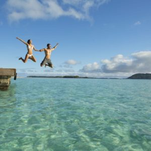 Tahiti Bora Bora Romantic Vacation Couple Jumping into Ocean Pier