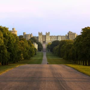 Windsor Castle royal palace military fort British monarch. The Long Walk ceremonial road lined with trees overlooked by the castle on a rise above Windsor Great Park.